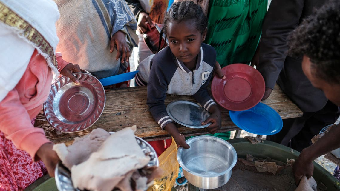 A displaced child from Western Tigray waits at meal time to receive a plate of food outside a classroom in the school where they are sheltering in Tigray's capital Mekele on February 24, 2021. For nearly two decades, the hilltop museum flanked by weeping willow trees showcased the military might of the Tigray region's ruling party, which dominated Ethiopian politics for decades. Located in the regional capital Mekele, the Tigray Martyrs' Monument housed weaponry and battle plans from the party's early days as a guerrilla movement, along with sepia portraits of men and women who lost their lives during its rise to power.