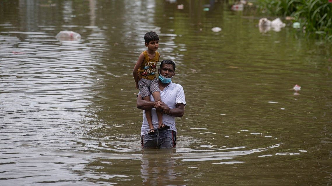 A Sri Lankan man wades through in an inundated street carrying a child following heavy rainfall at Malwana, on the outskirts of Colombo, Sri Lanka, June 5, 2021 (AP/Eranga Jayawardena)