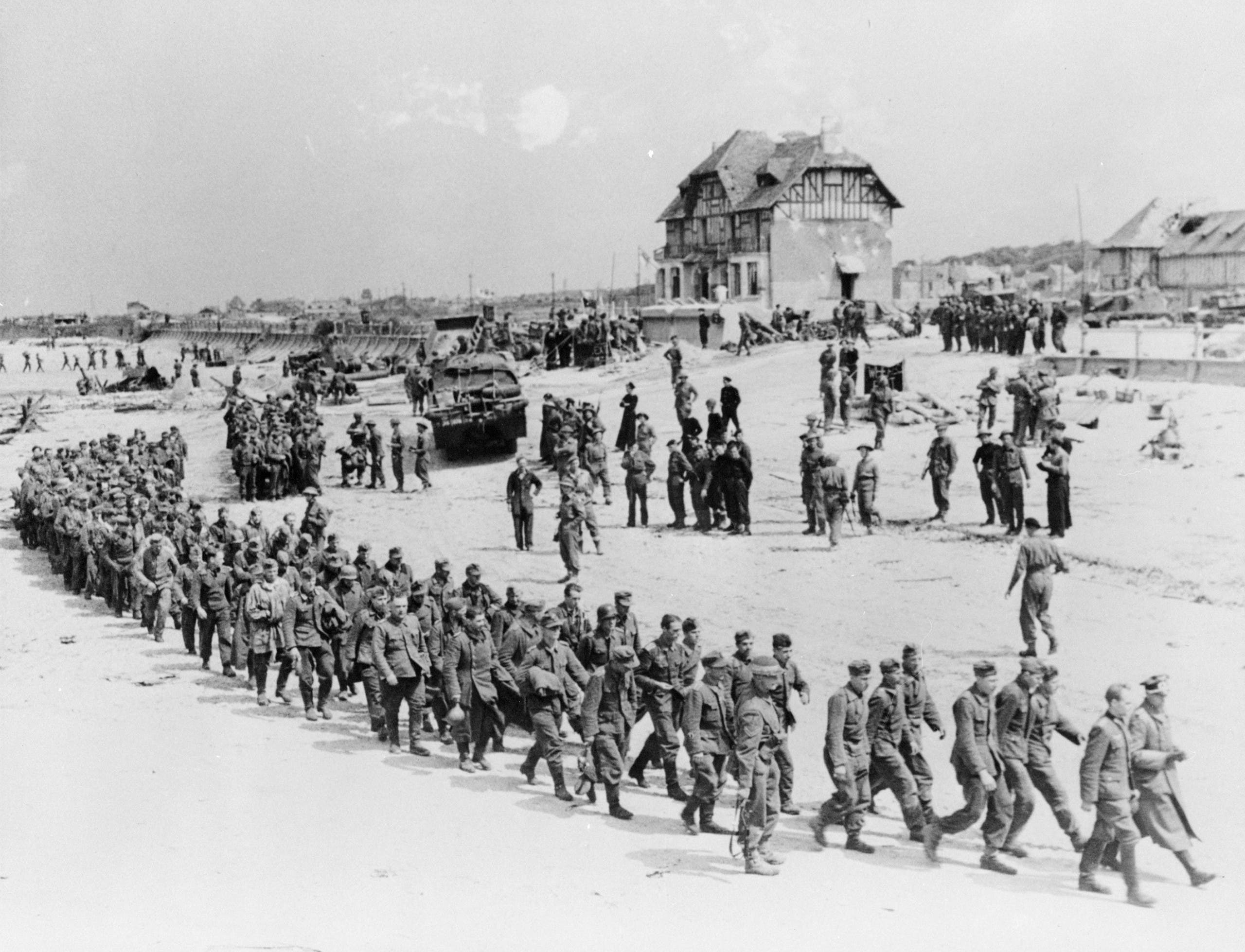 German prisoners-of-war march along Juno Beach landing area to a ship taking them to England, after they were captured by Canadian troops at Bernieres Sur Mer, France on June 6, 1944 in this handout photo provided by the National Archives of Canada. (Reuters)