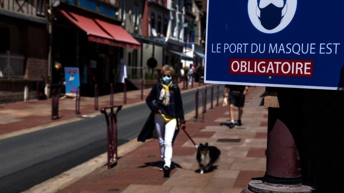 A woman walks past a sign indicating Face masks mandatory, in Houlgate, north-western France, on June 5, 2021. (Joel Saget/AFP)
