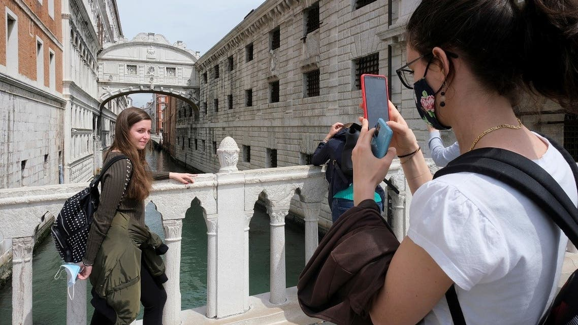 Tourists take pictures on a bridge as Italy lifts quarantine restrictions for travellers arriving from European Union countries, Britain and Israel and begins offering COVID-free flights in a bid to revive the tourism industry, in Venice, Italy, May 16, 2021. (Reuters)