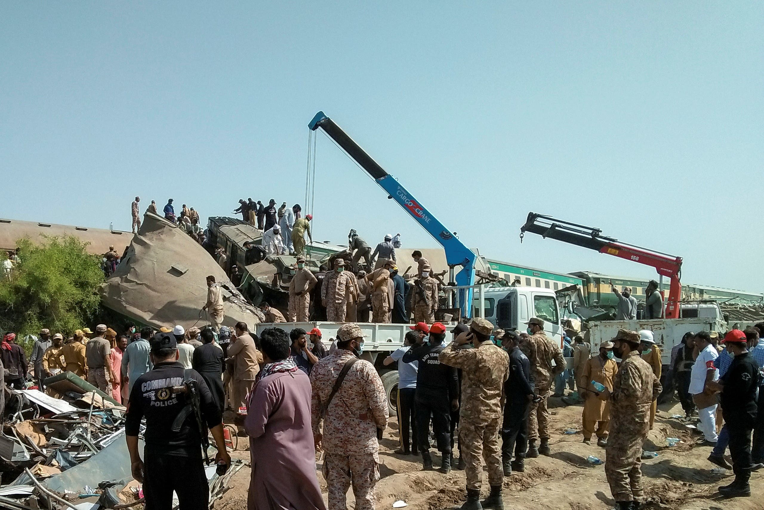 Paramilitary soldiers and rescue workers gather at the site following a collision between two trains in Ghotki, Pakistan June 7, 2021. (Reuters)