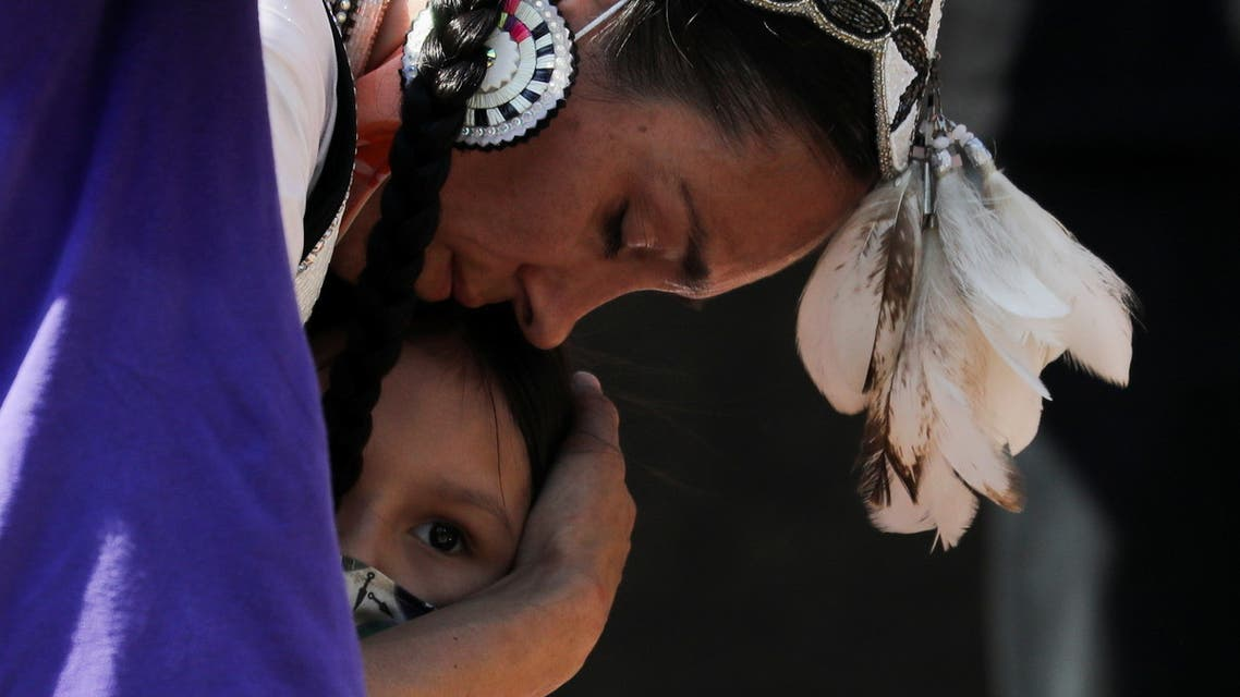 A woman embraces her daughter during a rally after the remains of 215 children were found at a residential school, in Toronto, Ontario, Canada June 6, 2021. (Reuters)