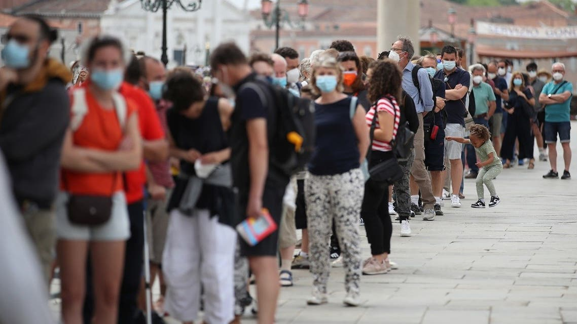 """People queue to enter San Marco Dome, as the region of Veneto becomes a """"white zone,"""" following a relaxation of COVID-19 restrictions with only masks and social distancing required, in Venice, Italy, June 7, 2021. (Reuters/Yara Nardi)"""