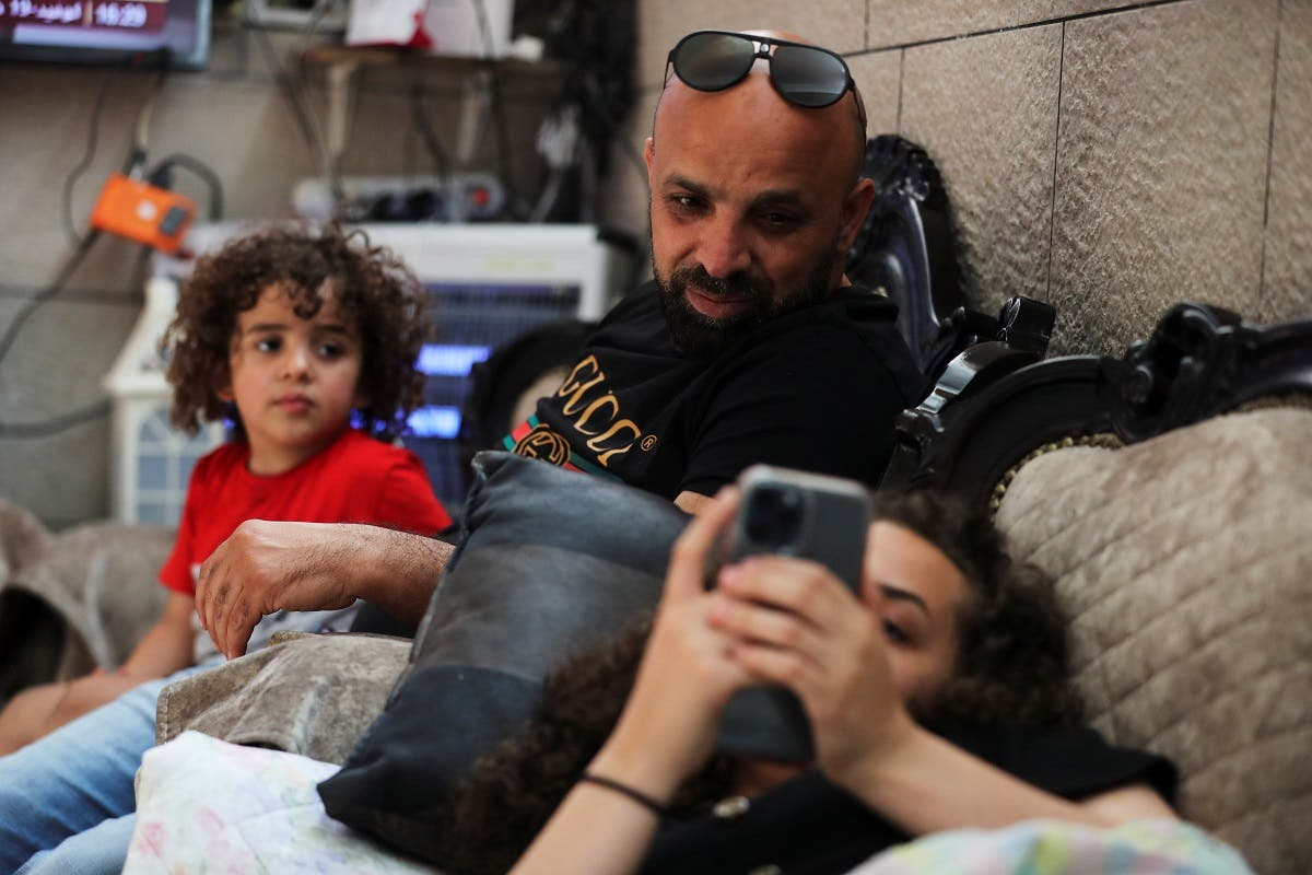Mohammed, father of Jana Kiswani, 16, sits next to his daughter as she rests at home in the Sheikh Jarrah neighborhood of East Jerusalem May 27, 2021. Picture taken May 27, 2021. (Reuters/Ammar Awad)