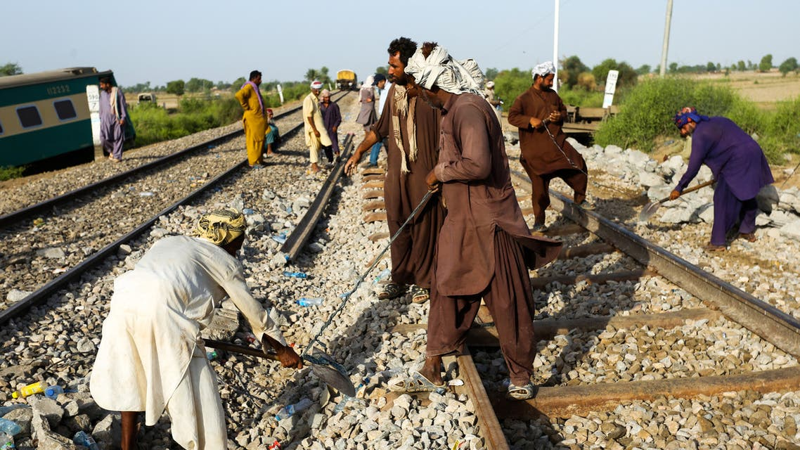 Railway workers fix the track in Daharki on June 8, 2021, a day after a packed inter-city train ploughed into another express that had derailed, killing at least 63 people. (File photo: AFP)