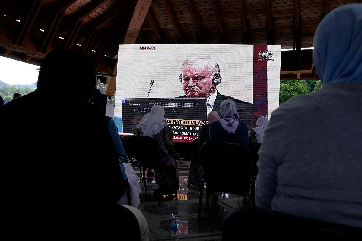 Women from Srebrenica watch a live broadcast from the Yugoslav War Crimes Tribunal in The Hague to learn the verdict for Bosnian Serb military chief Ratko Mladic, on the screen, at the memorial cemetery in Potocari near Srebrenica, eastern Bosnia, Tuesday, June 8, 2021. (AP/Darko Bandic)