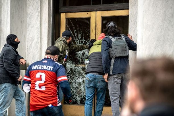 Far-right protesters break the door to the Capitol building during a protest against restrictions to prevent the spread of coronavirus disease (COVID-19) in Salem, Oregon, US, December 21, 2020. (Reuters)