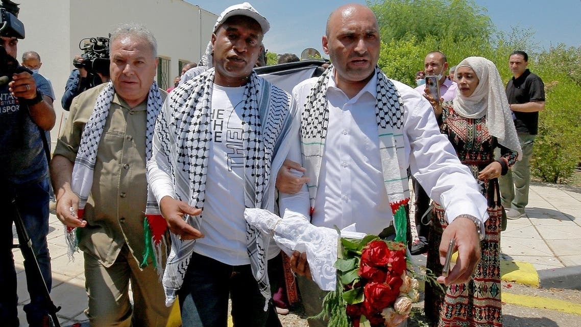 Palestinian-Jordanian Abdullah Abu Jaber, who was jailed in Israel after planting a bomb on a bus that wounded 13 civilians in 2000, is welcomed by his family upon his release at the Sheikh Hussein Crossing between Jordan and Israel on June 8, 2021. (AP)