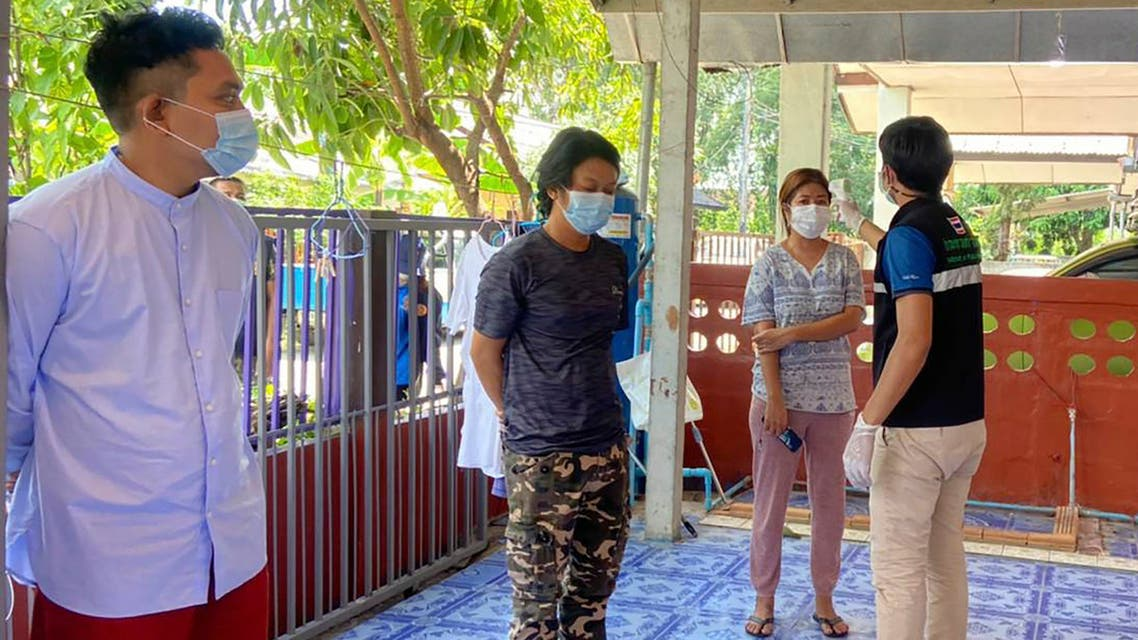 In this May 9, 2021, file photo released by the San Sai District Administrative Office, a Thai officer checks the temperature of journalists working for Democratic Voice of Burma, at San Sai District in Chiang Mai province north of Thailand. (AP)