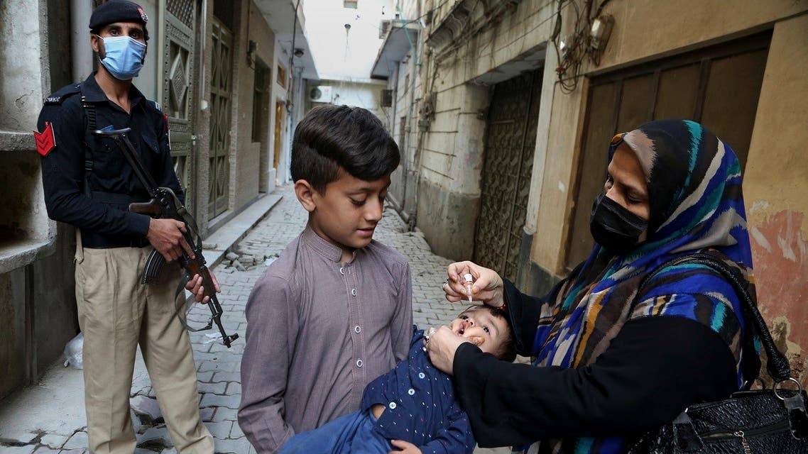 A Police officer stands guard while a health worker administers a polio vaccine to a child, in Peshawar, Pakistan, on March 29, 2021. (AP)