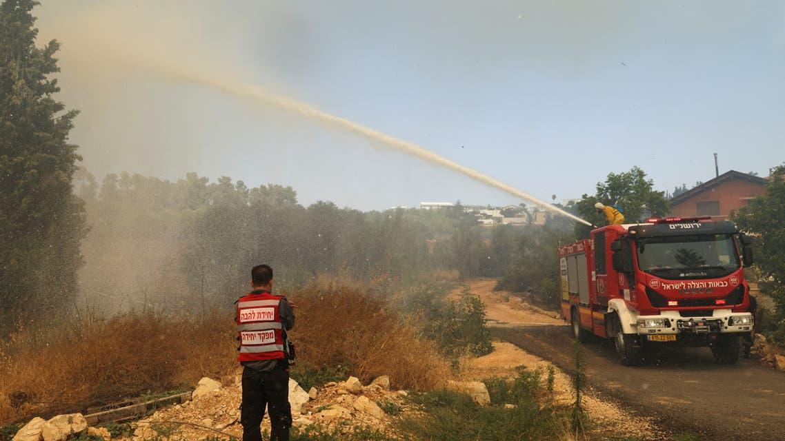 A fire-fighting plane disperses fire retardant as it assists in extinguishing a fire near Kibbutz Maale Hahamisha in Israel, in the outskirts of Jerusalem June 9, 2021. REUTERS/Ronen Zvulun