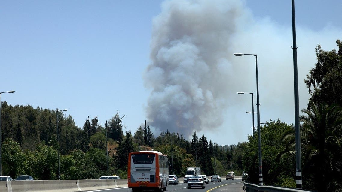 Cars drive on a highway as smoke billows from a forest fire in the area of the Arab-Israeli village of Abu Ghosh near Jerusalem, on June 9, 2021. (Emmanuel Dunand/AFP)
