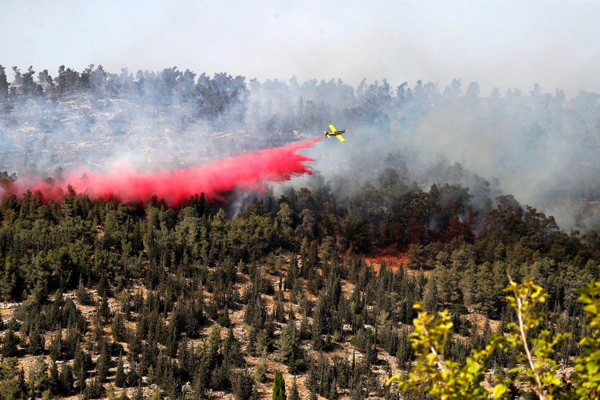 A firefighting plane works on extinguishing a fire raging in a forest area near Kibbutz Neve Ilan west of Jerusalem, on June 9, 2021. (Ahmad Gharabli/AFP)
