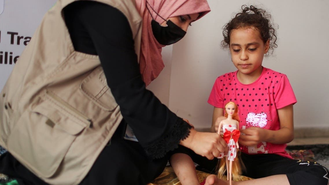 A psychologist plays with Palestinian girl Suzy Eshkuntana, who was pulled out from the rubble of her house, destroyed by an Israeli airstrike, as part of a mental health support session in Gaza City, June 3, 2021. (Reuters/Mohammed Salem)