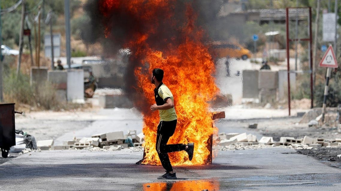 A Palestinian demonstrator runs past a burning barricade during clashes with Israeli forces at a protest against Israeli settlements, near Nablus in the Israeli-occupied West Bank, June 8, 2021. (Reuters)