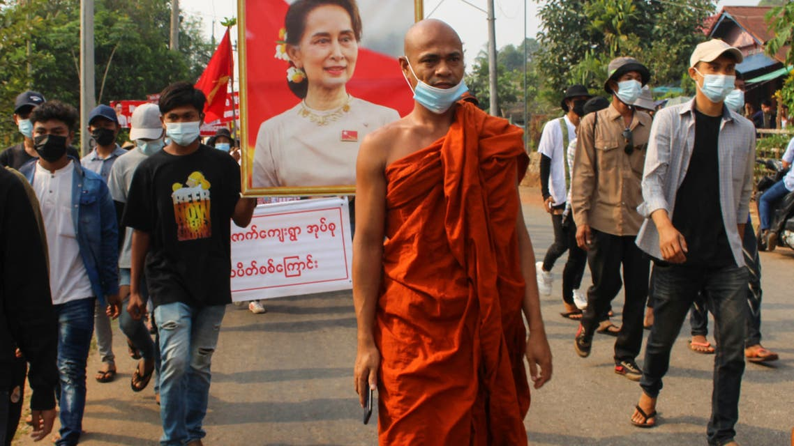 This handout photo taken and released by Dawei Watch on March 27, 2021 shows a Buddhist monk walking with protesters, as a portrait of detained civilian leader Aung San Suu Kyi is held aloft, during a demonstration against the military coup in Dawei. (File photo: AFP)