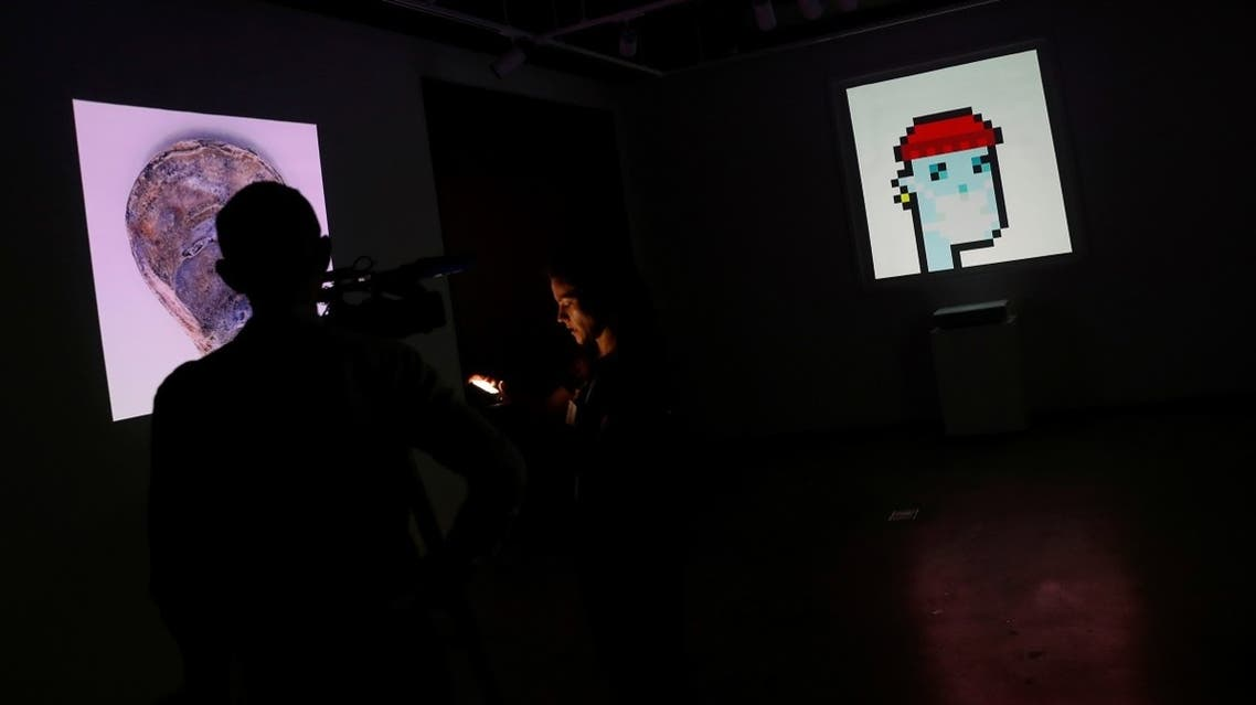 """A television crew is seen next to the non-fungible token (NFT) """"CryptoPunk #7523,""""a series of 10,000 unique pixel-art characters made by Larva Labs in 2017, during a media preview for the """"Natively Digital: A Curated NFT Sale"""" auction at Sotheby's in New York City, US, on June 4, 2021. (Reuters)"""