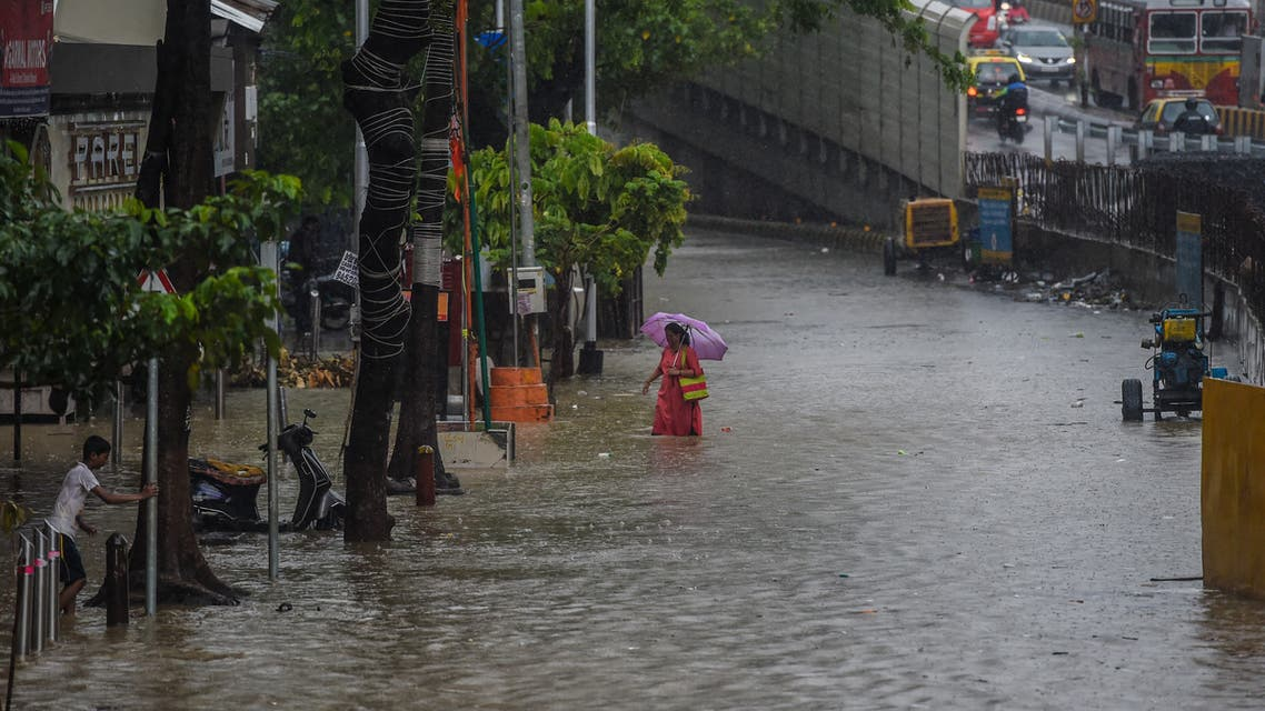 A woman walks on a flooded road during heavy monsoon rains in Mumbai on June 9, 2021.. (File Photo: AFP)