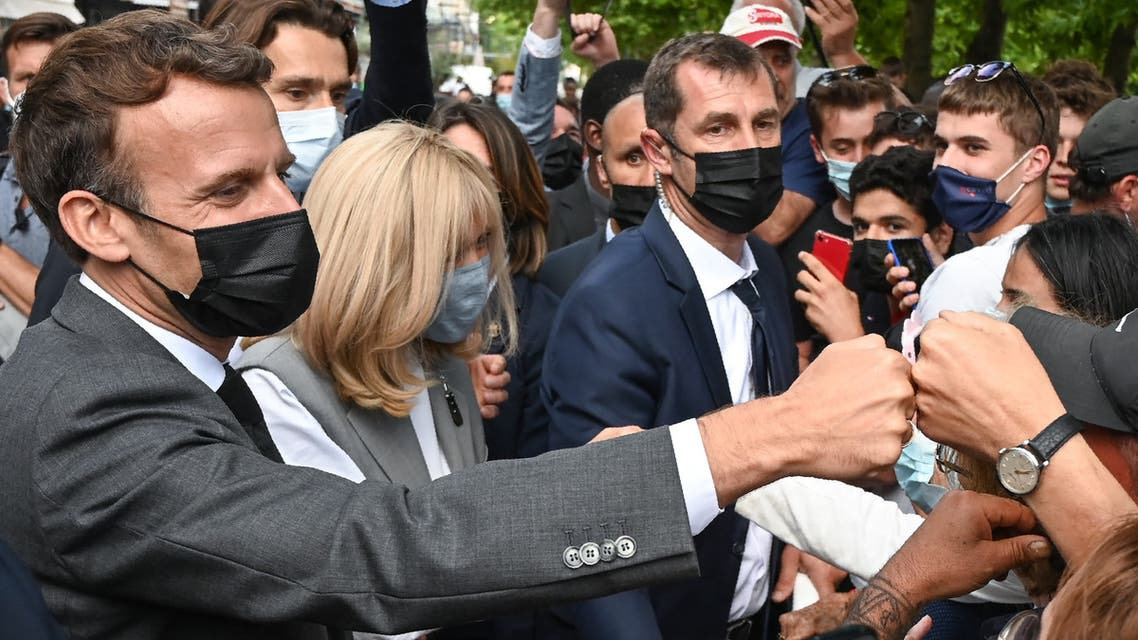French President Emmanuel Macron (L) and his wife Brigitte Macron (C) interact with members of a crowd while visiting Valence on June 8, 2021 during a visit in the French southeastern department of Drôme, the second stage of a nationwide tour ahead of next year's presidential election. (AFP)