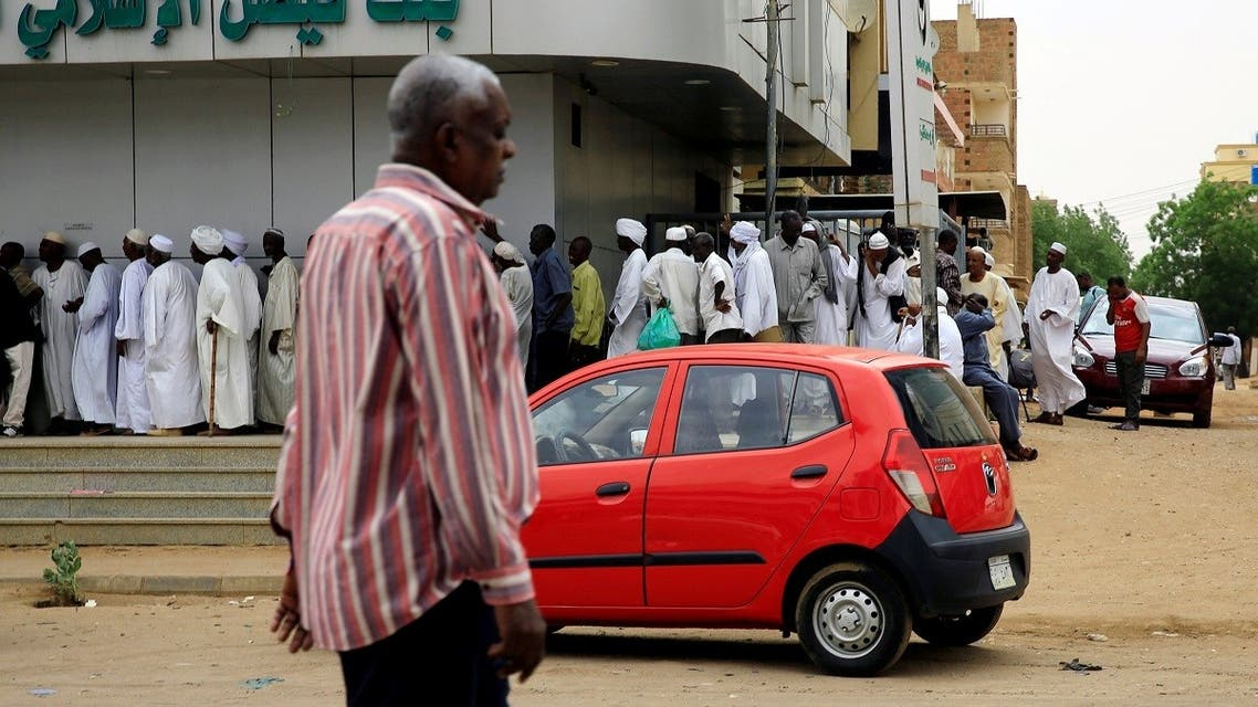 Sudanese customers queue to access money services at the Faisal Islamic Bank (Sudan) in Khartoum. (Reuters)