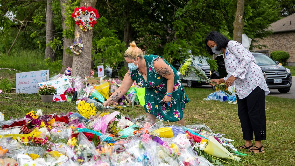 People are seen at a makeshift memorial at the fatal crime scene where a man driving a pickup truck jumped the curb and ran over a Muslim family in what police say was a deliberately targeted anti-Islamic hate crime, in London, Ontario, Canada June 9, 2021. (Reuters)