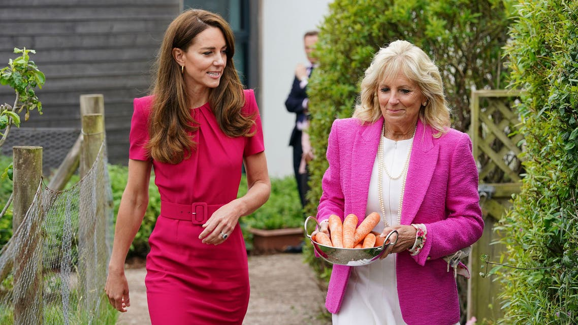 Britain's Kate, Duchess of Cambridge, left, and US First Lady Jill Biden, carrying carrots for the school rabbit, Storm, during a visit to Connor Downs Academy in Hayle, West Cornwall, during the G7 summit in England, Friday, June 11, 2021. (AP)