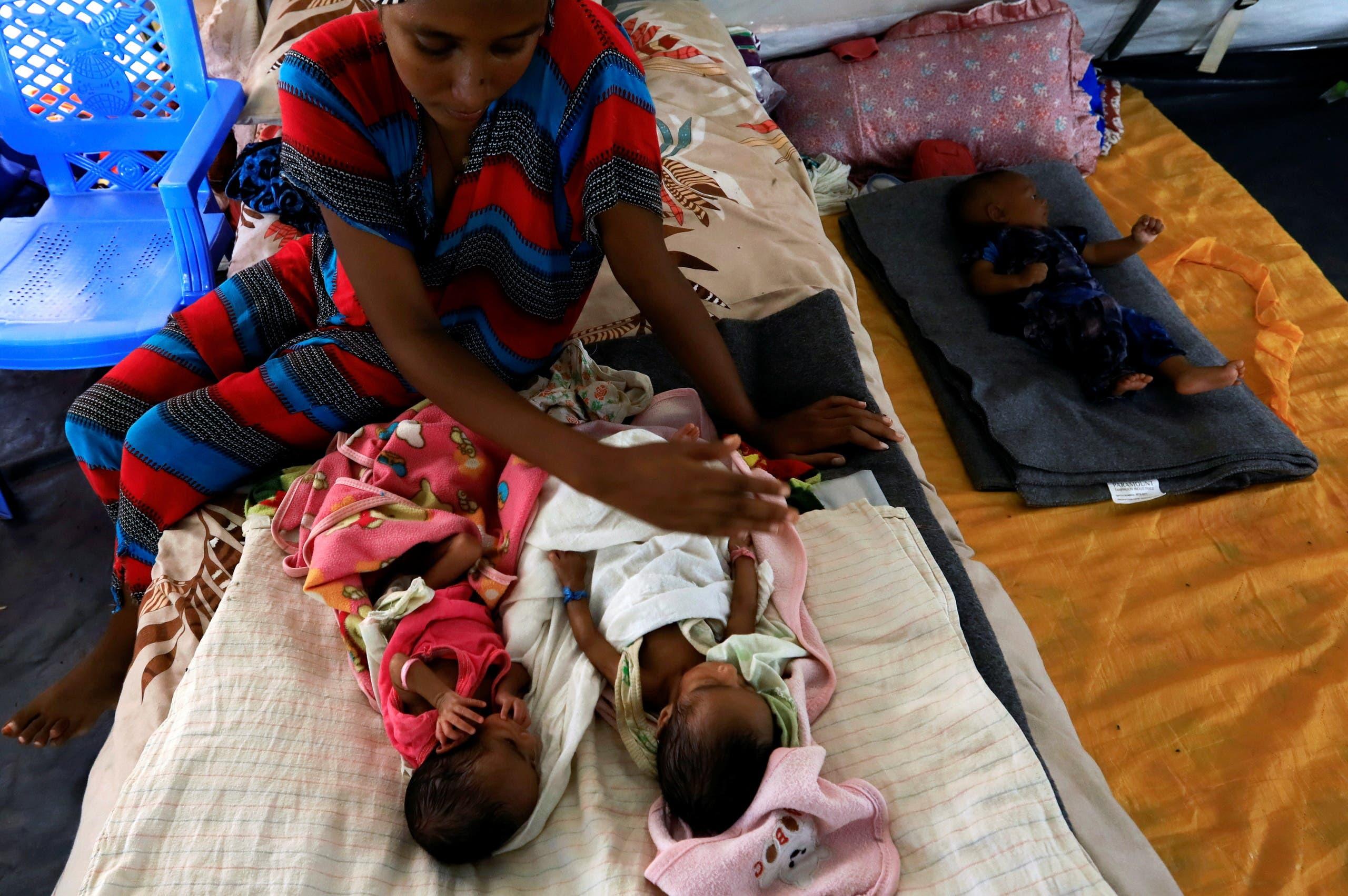 أم مع أطفالها في مستشفى بإقليم تيغراي الإثيوبي - رويترز