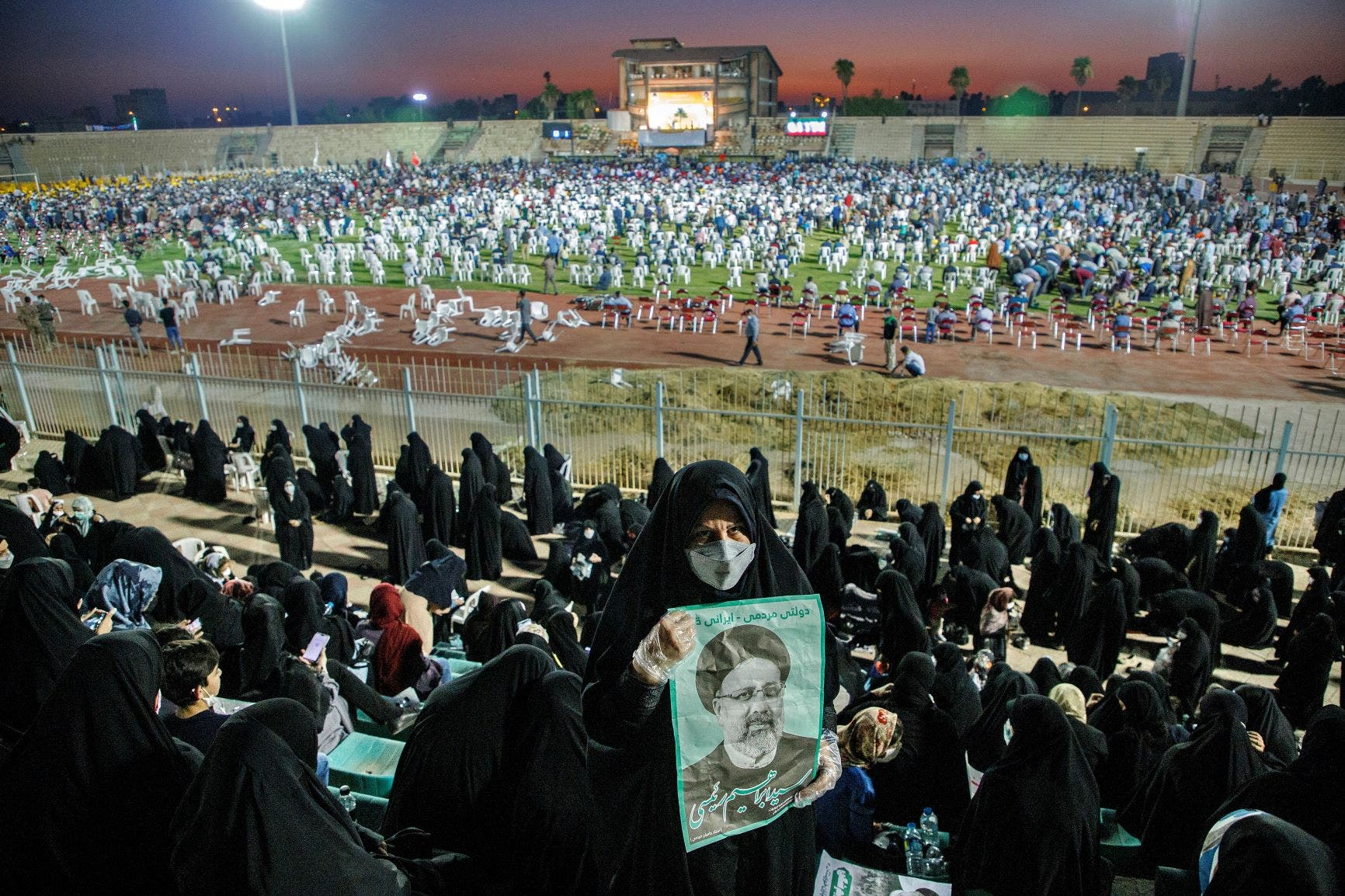 In this Wednesday, June 9, 2021, photo, a supporter of the presidential candidate Ebrahim Raisi, currently judiciary chief, hold posters of him during a campaign rally at the Takhti Stadium in Ahvaz, Iran. (AP)