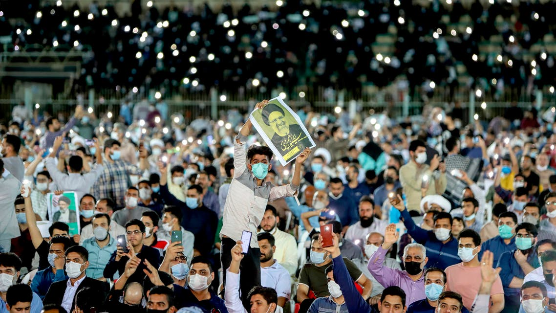 In this Wednesday, June 9, 2021 photo, a supporter of the presidential candidate Ebrahim Raisi, currently judiciary chief, hold his posters during a campaign rally at the Takhti Stadium in Ahvaz, Iran. (AP)