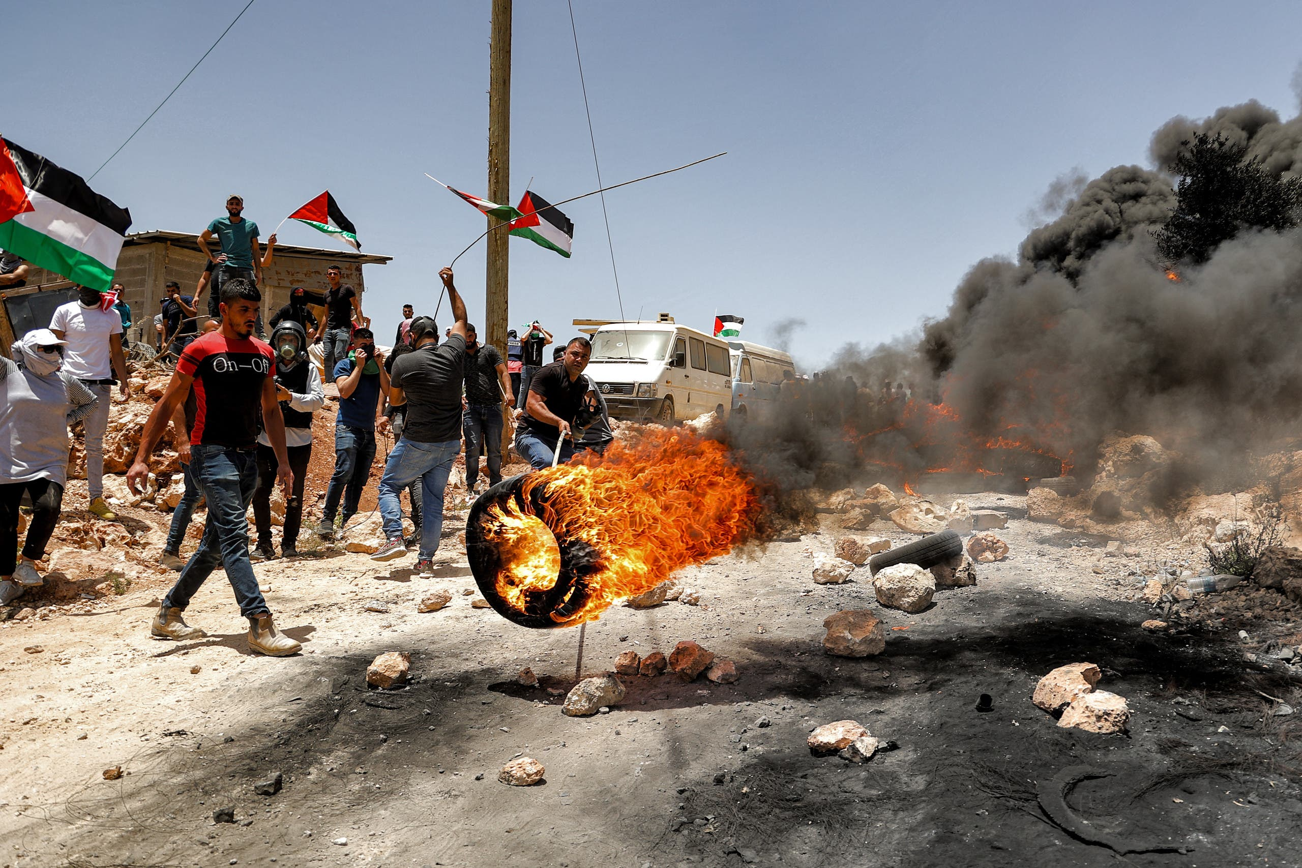 Palestinian protesters set tires aflame during clashes with Israeli security forces following a demonstration in the village of Beita, south of Nablus, in the occupied West Bank on June 11, 2021. (AFP)
