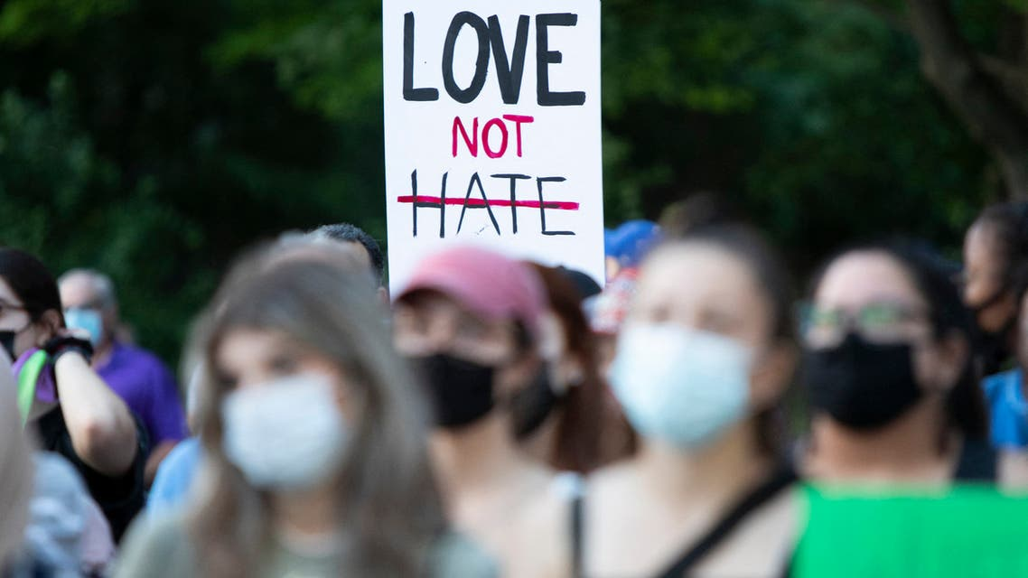 """People hold a sign reading """"Love Not Hate"""" at the London Muslim Mosque during the multi-faith march to end hatred, after a man driving a pickup truck struck and killed four members of a Muslim family in London, Ontario, Canada on June 11, 2021. (AFP)"""