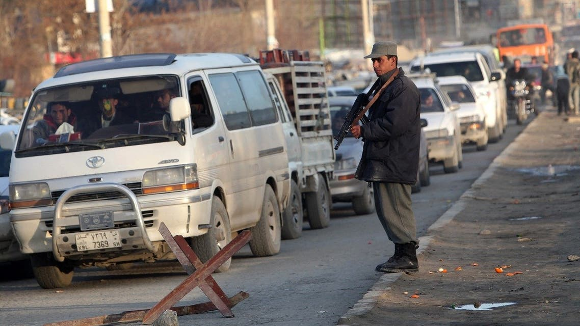 A file photo shows an Afghan policeman stands guard at a check point in a neighborhood of the capital Kabul on March 1, 2010. (AFP/Behrouz Mehri)