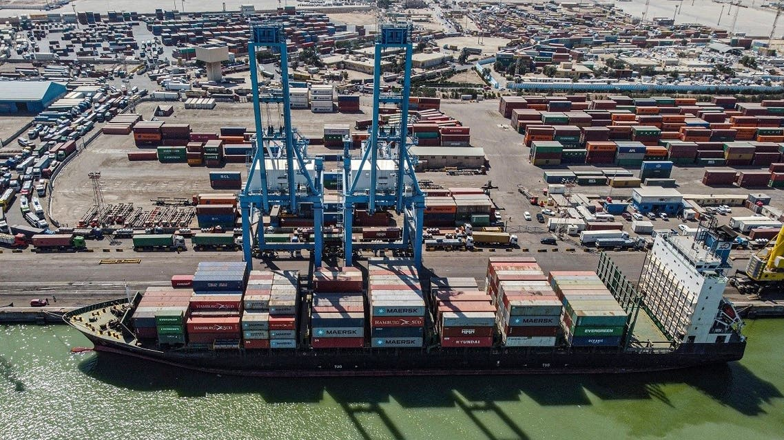 This picture taken on March 14, 2021 shows an aerial view of containers being unloaded off a cargo ship moored at the port of Umm Qasr, south of Iraq's southern city of Basra. (Hussein Faleh/AFP)