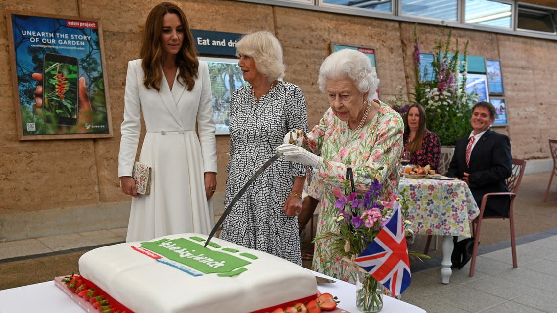Britain's Queen Elizabeth attempts to cut a cake with a sword next to Camilla, Duchess of Cornwall, and Catherine, Duchess of Cambridge as they attend a drinks reception on the sidelines of the G7 summit, at the Eden Project in Cornwall, Britain June 11, 2021. (Reuters)