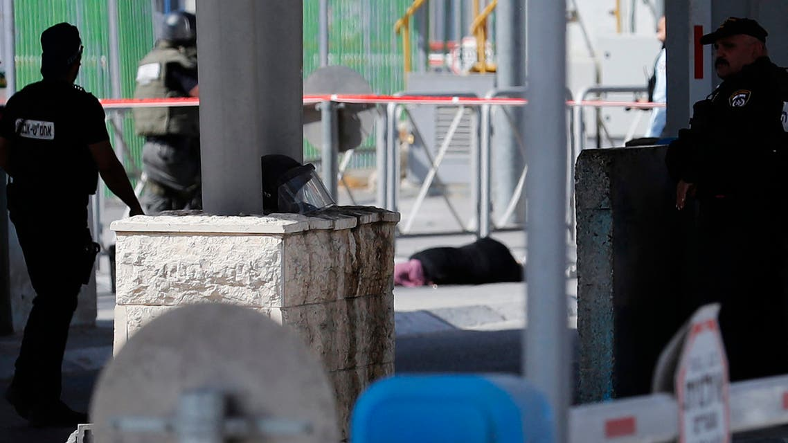 Israeli security forces look at a woman's body on the ground after she was shot by a guard at the Qalandia checkpoint between the occupied West Bank. (AFP)