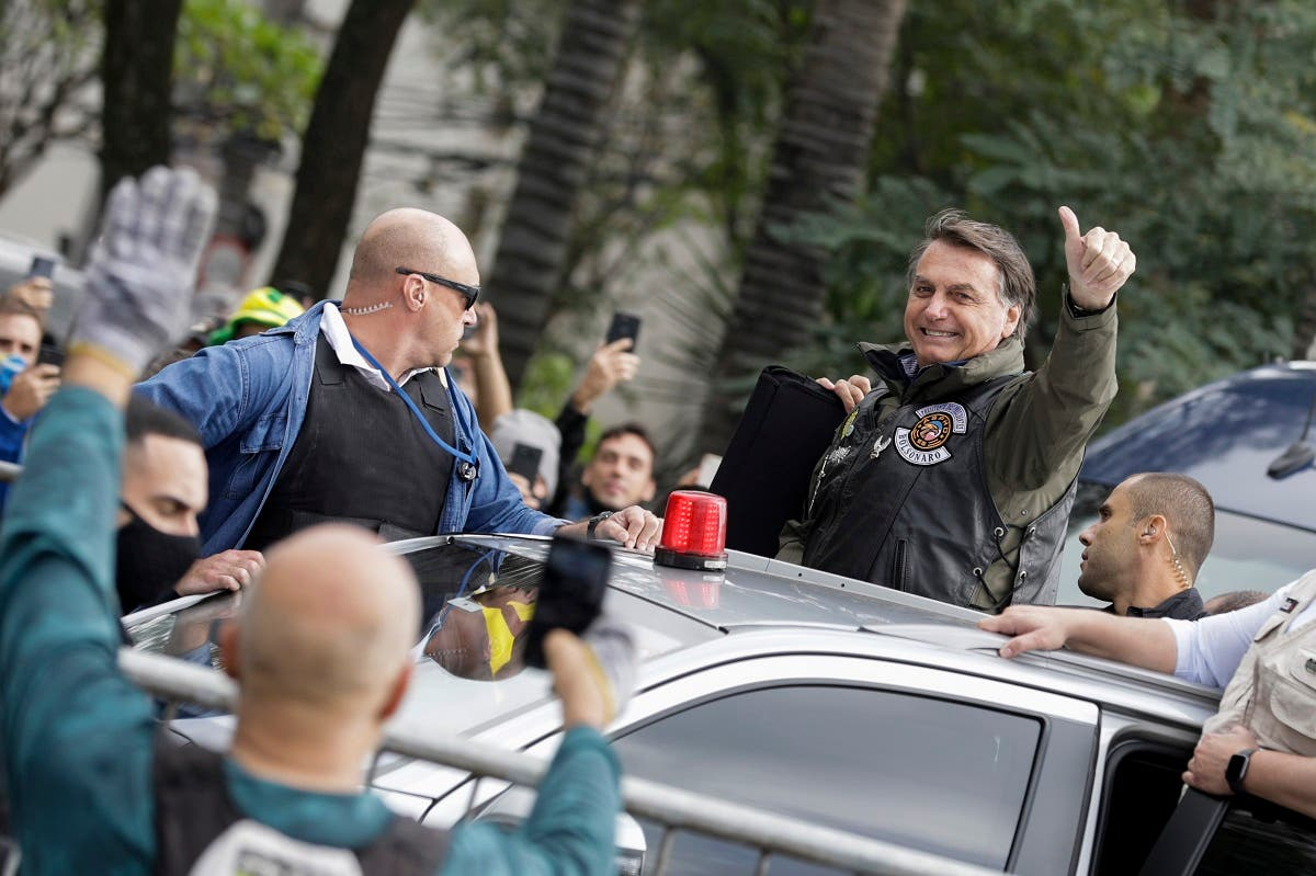 Bolsonaro flashes a thumbs up as he arrives to take part in caravan of motorcycle enthusiasts in a show of support for Bolsonaro, in Sao Paulo, Brazil, June 12, 2021. (AP/Marcelo Chello)