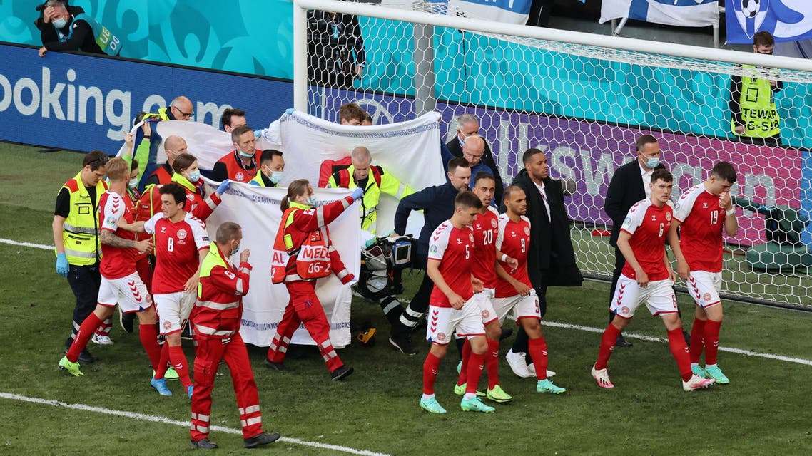 Denmark's Christian Eriksen is stretchered off the pitch after collapsing during the match as his teammates react. (Reuters)