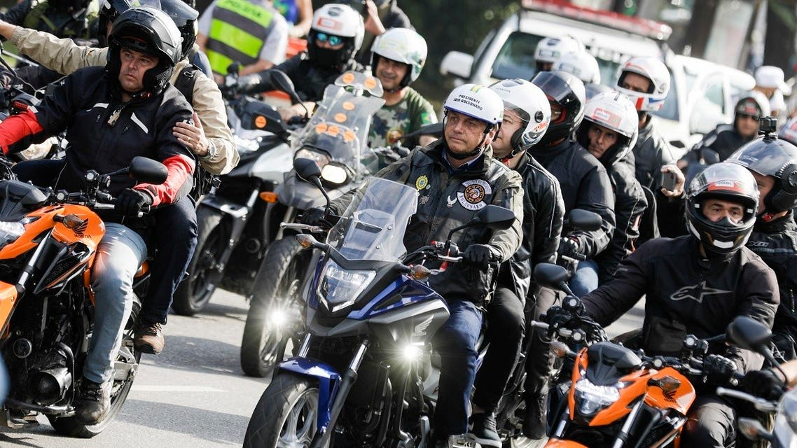 Brazil's President Jair Bolsonaro, center, takes part in a caravan of motorcycle enthusiasts who gathered in a show of support for Bolsonaro, in Sao Paulo, Brazil, June 12, 2021. (AP/Marcelo Chello)
