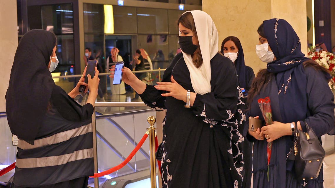 A picture taken late on June 3, 2021 shows Saudi staff checking attendant's mobiles for vaccine certificates or a negative Covid-19 test, at the entrance of a theatre hosting the first concert in the Saudi capital Riyadh since the start of the COVID-19 pandemic. (AFP)