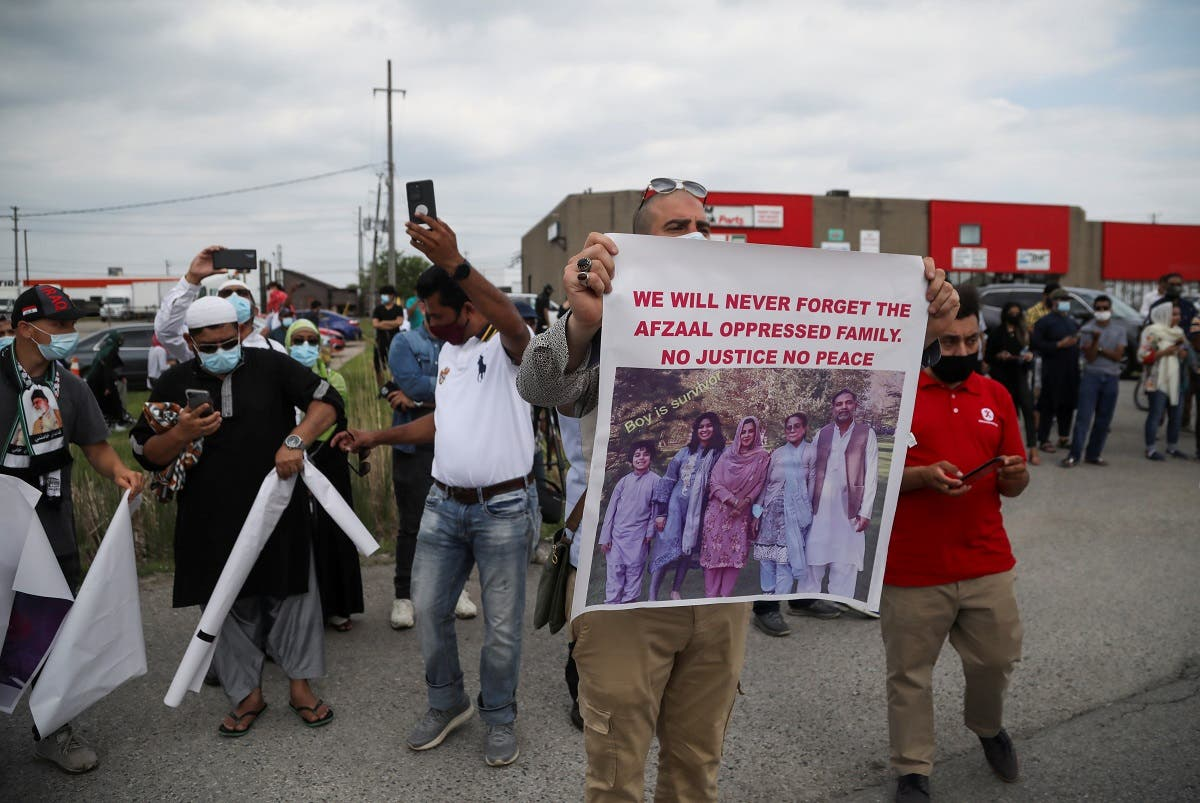 """A man holds a banner after a funeral of the Afzaal family that was killed in what Canadian PM Trudeau describes as a """"terrorist attack"""", outside the Islamic Centre of Southwest Ontario, in London, Ontario, Canada June 12, 2021. (Reuters/Carlos Osorio)"""