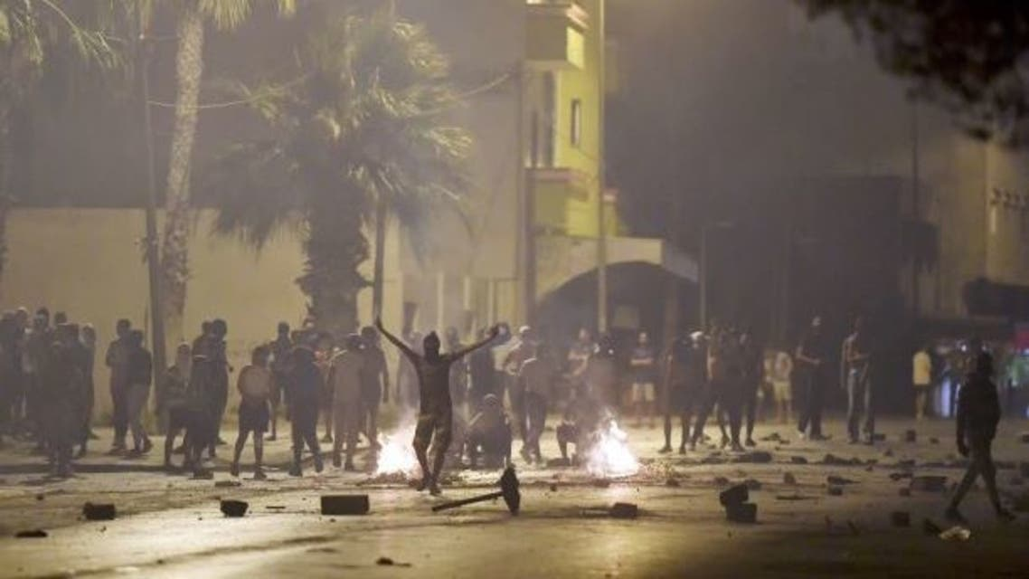 Protesters blocking a street gesture as Tunisian security forces fire tear gas in the Sidi Hassine suburb on the northwestern outskirts of Tunis on June 12, 2021, amid outrage against policing practices following the death of a youth. (AFP)