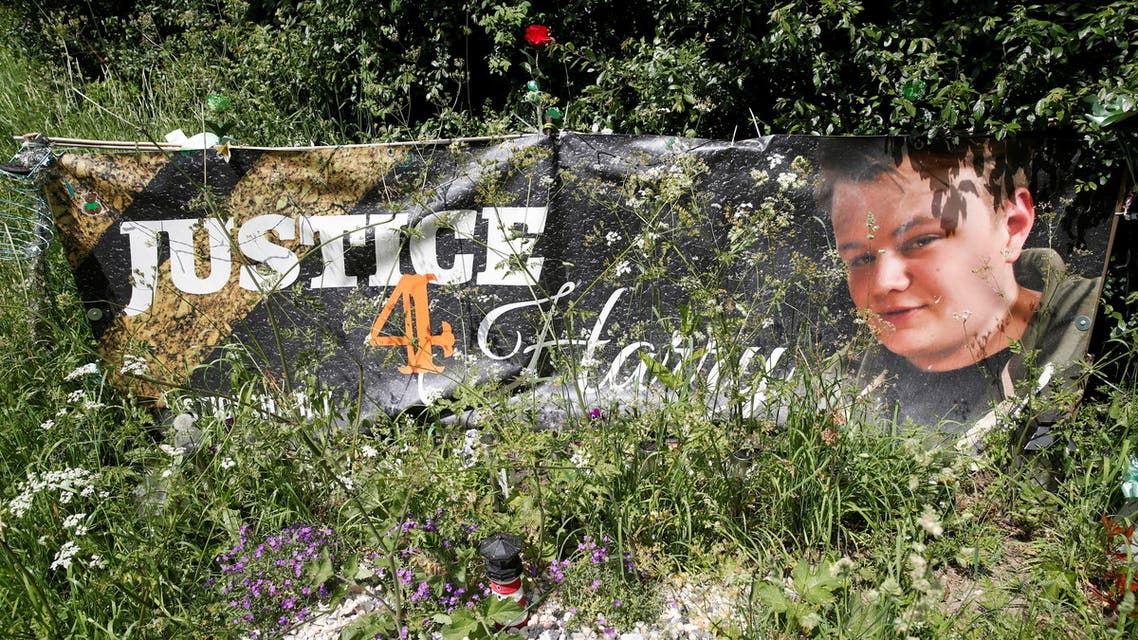 A banner and a memorial area for British teenager Harry Dunn who died in a road traffic collision is pictured near to the entrance of RAF Croughton, in Croughton, near Brackley, Britain June 11, 2021. REUTERS/Andrew Boyers
