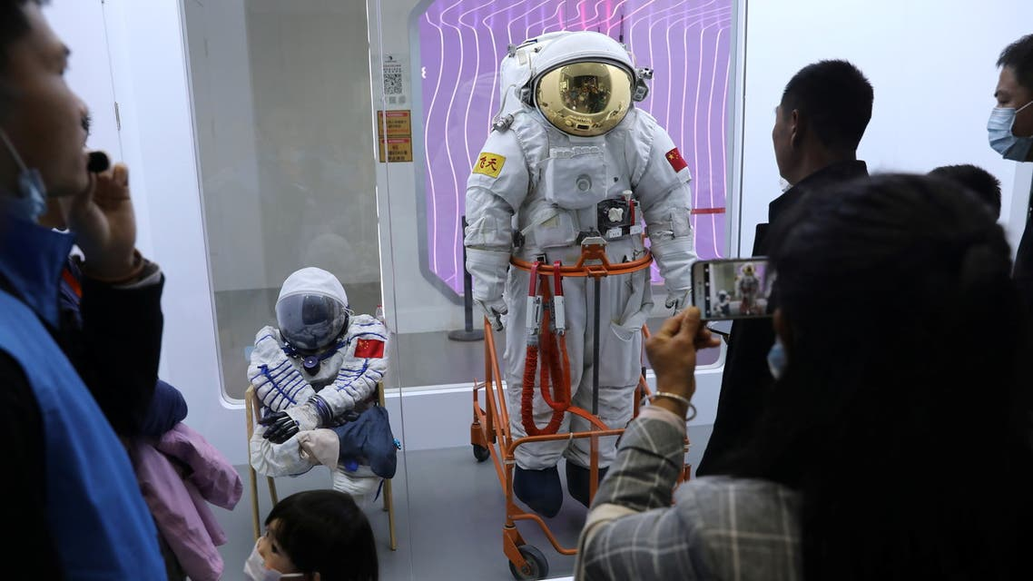Visitors look at space suits worn by Chinese astronauts from manned space program, at an exhibition featuring the development of China's space exploration on the country's Space Day at China Science and Technology Museum in Beijing, China April 24, 2021. REUTERS/Tingshu Wang