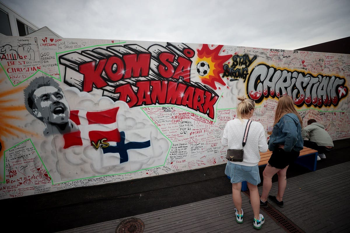 People write get well messages on a wall at a fanzone in Copenhagan on June 14, 2021, after Denmark's Christian Eriksen collapsed on the pitch during his side's Euro 2020 match with Finland. (Reuters)