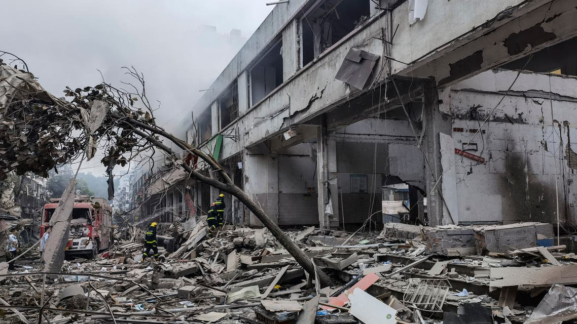 Workers search for victims in a building damaged by a gas line explosion which left at least 12 people dead and nearly 140 others injured in Shiyan, in central China's Hubei province on June 13, 2021. (AFP)