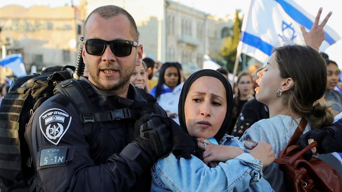 An Israeli policeman removes a Palestinian woman from the area as youth from far-right Israeli groups participate in a flag-waving procession at Damascus Gate, just outside Jerusalem's Old City June 15, 2021. (Reuters/Ammar Awad)