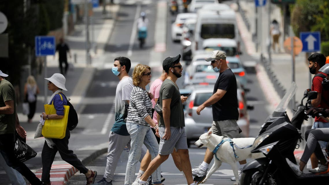 Pedestrians cross a street as Israel rescinds the mandatory wearing of face masks outdoors in the latest return to relative normality, boosted by a mass-vaccination campaign against the coronavirus disease (COVID-19) pandemic, in Tel Aviv, Israel April 18, 2021. (Reuters)