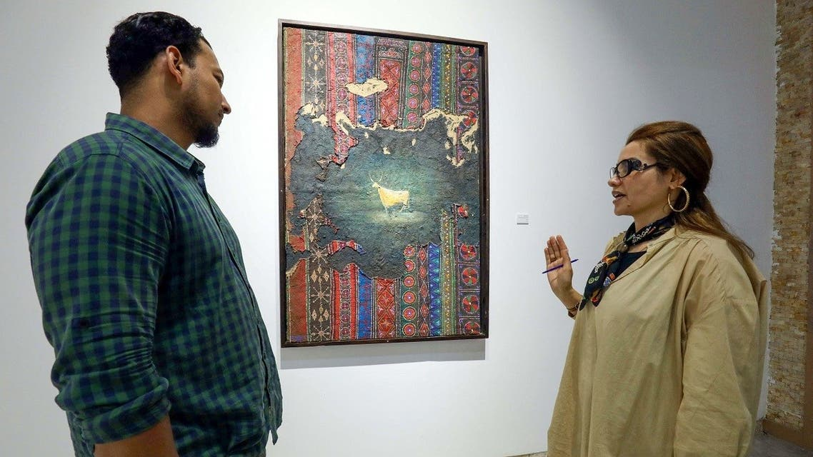 A visitor talks to Libyan artist Elham el-Ferjani in front of one of her works at the Hamim Gallery in the eastern city of Benghazi on June 14, 2021. (Abdullah Doma/AFP)