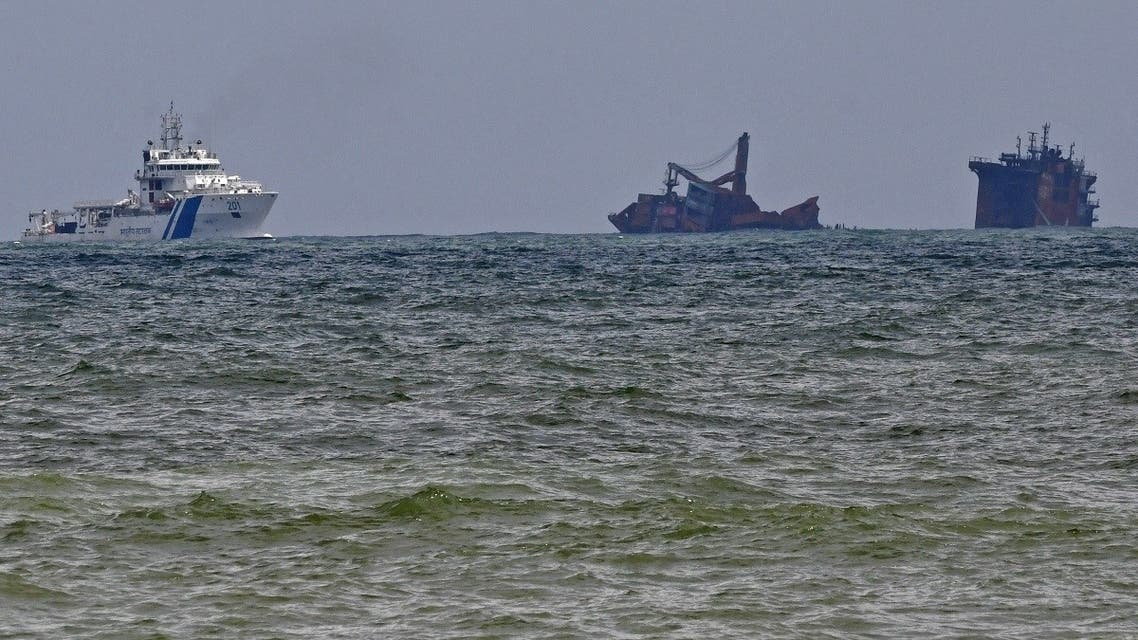 An Indian Coast Guard ship (L) approaches near the Singapore-registered container ship MV X-Press Pearl that partially sunk after burning for almost two weeks, just outside Colombo's harbor on June 4, 2021. (Lakruwan Wanniarachchi/AFP)